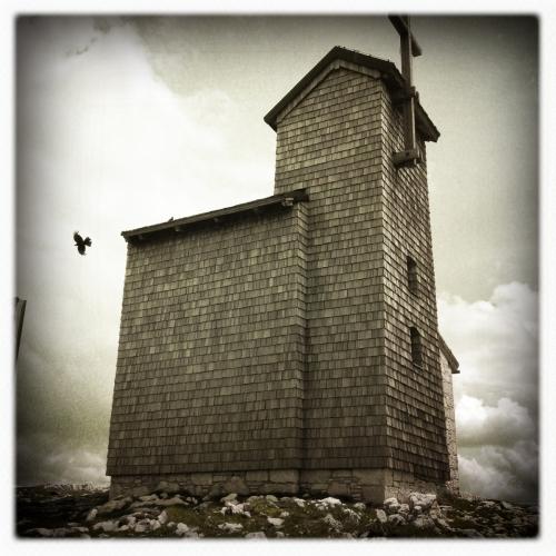 Vogel und Holzkirche auf dem Berg